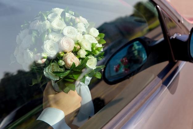 Жених сидит в машине с букетом для невесты