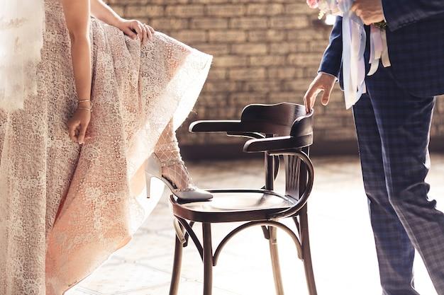 花束を持った新郎と新婦が椅子に足を置き、靴を見せます。