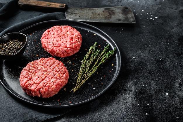 牛ひき肉のパテ、ひき肉のカツレツ。黒の背景