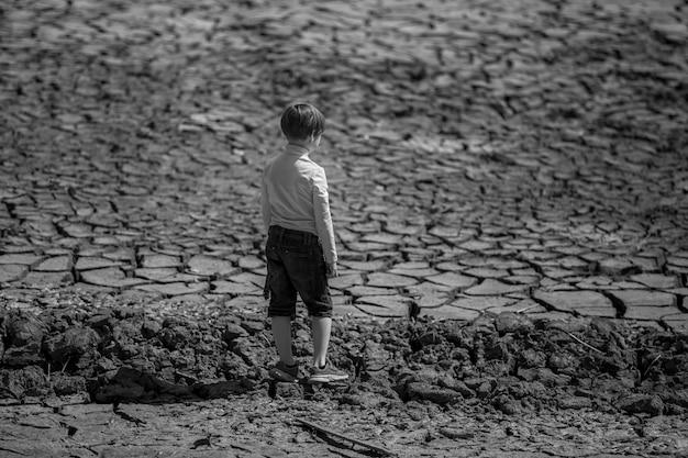 땅이 건조하고 갈라졌습니다. 지구 온난화의 배경 인 사막. 소년은 중앙에 서 있습니다.