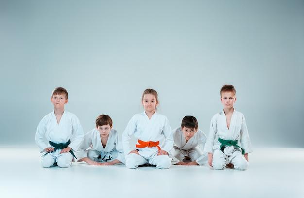 Группа юношей и девушек воюет на занятиях по айкидо в школе боевых искусств. концепция здорового образа жизни и спорта