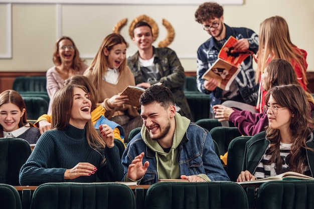 수업 전에 강당에 앉아 쾌활한 행복한 학생들의 그룹