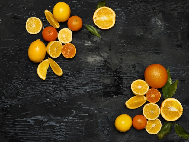 Группа свежих фруктов - лимоны и мандарины на фоне черного пространства