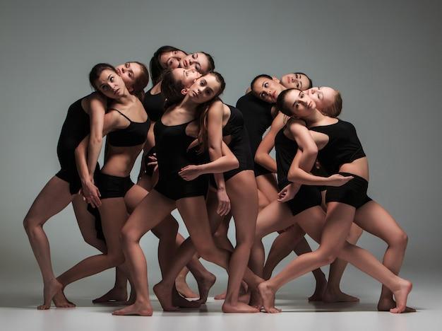 Группа современных артистов балета танцует на сером фоне