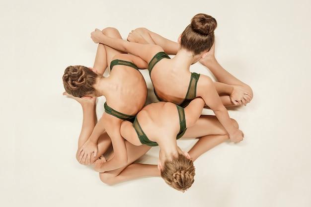 Группа современных артистов балета танцует на сером фоне студии. вид сверху