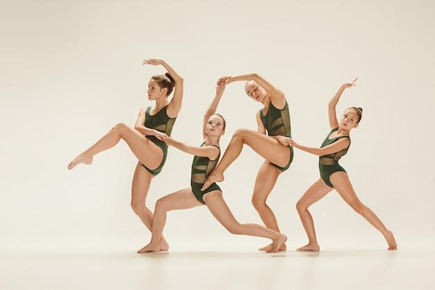 Группа современных артистов балета танцует на сером фоне студии