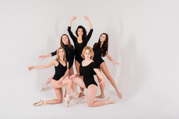 흰색 스튜디오에서 검은색 바디수트를 입은 현대 발레 댄서 그룹
