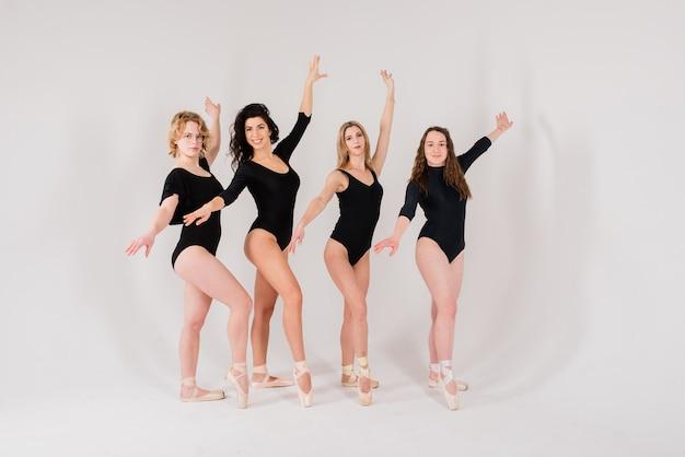 Группа современных артистов балета в черном боди в белой студии