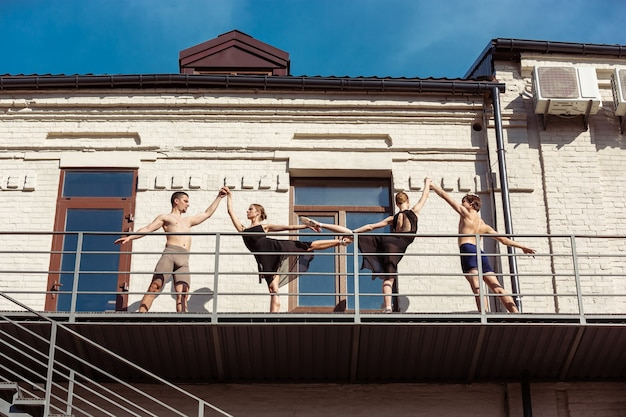 Группа артистов современного балета на лестнице города.