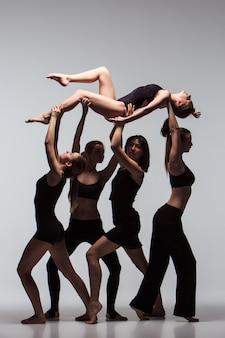 Группа современных артистов балета позирует на сером фоне.