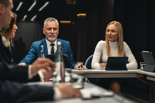 ビジネス会議のテーブルに座っている人々のグループ