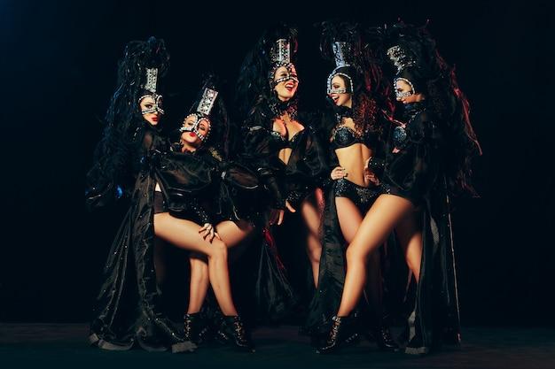 검은 스튜디오 배경에서 포즈를 취한 카니발 드레스를 입은 젊은 행복한 미소 짓는 아름다운 여성 무용수들