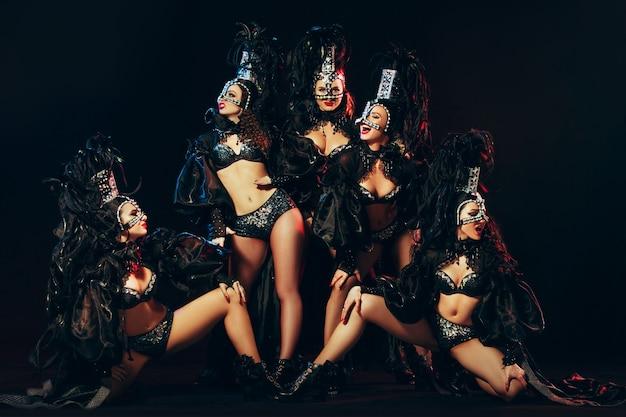 검은 스튜디오 배경에서 포즈를 취한 카니발 드레스를 입은 젊은 행복한 미소 짓는 아름다운 여성 댄서들