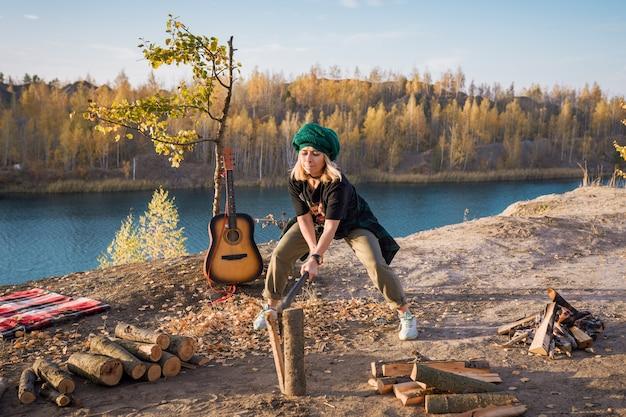 Группа молодежи отдыхает на природе. девушка рубит дрова для костра топором.