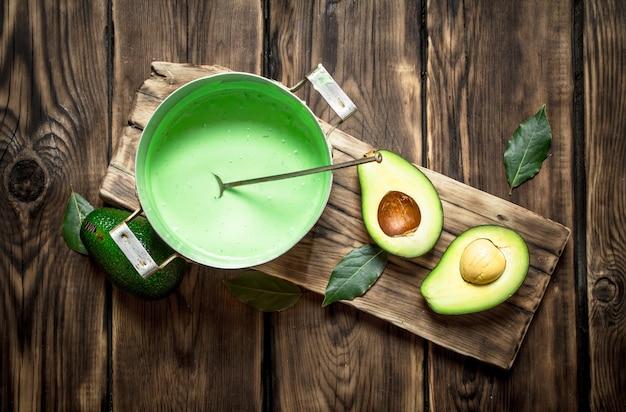 보드에있는 아보카도 소스와 채소. 나무 배경.