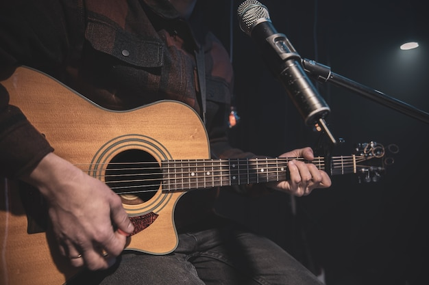 기타리스트가 마이크 앞에서 카포를 들고 어쿠스틱 기타를 연주합니다.