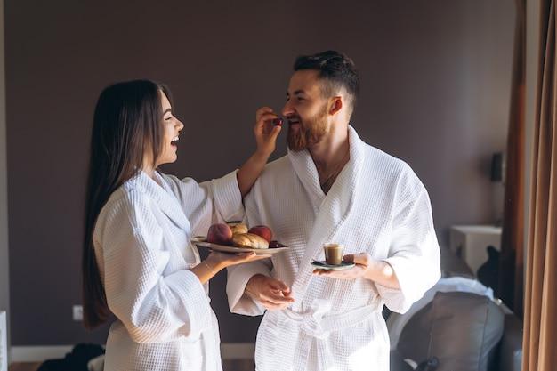 Парень и девушка халат, девушка кормит парня фруктами