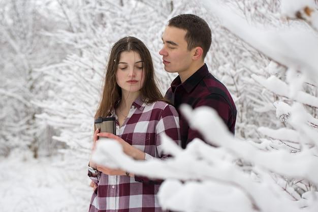 남자와 여자는 겨울 숲에서 휴식을 취한다 남편과 아내 눈 속에서 젊은 부부