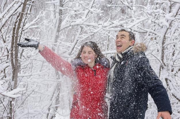 남자와 여자는 겨울 숲에서 휴식을 취합니다. 눈 속에서 남편과 아내입니다.
