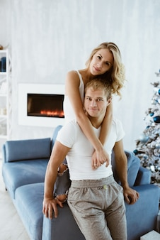 남자와 여자는 포옹하고 파란 소파에 키스. 크리스마스 트리 장식. 전자 벽난로. 흰색 티셔츠와 청바지에 금발입니다.