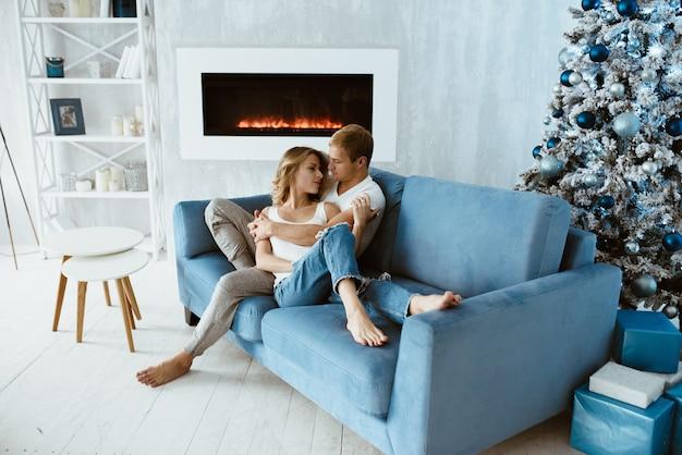 남자와 여자는 포옹하고 파란 소파에 키스. 장난감으로 장식 된 크리스마스 트리입니다. 전자 벽난로.