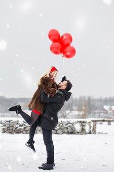 남자는 발렌타인 데이에 여자 친구를 팔로 빙빙 돌고 있습니다.