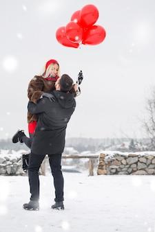 남자는 발렌타인 데이에 그의 여자 친구를 팔에 맴돌고 있습니다.