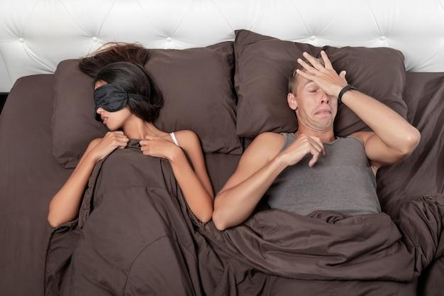 남자는 잠을 자려고 이마에 박수를 치고 여자 친구는 달콤하게 자고 있습니다.