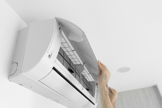 그 사람은 집 에어컨 필터를 먼지로부터 청소합니다.