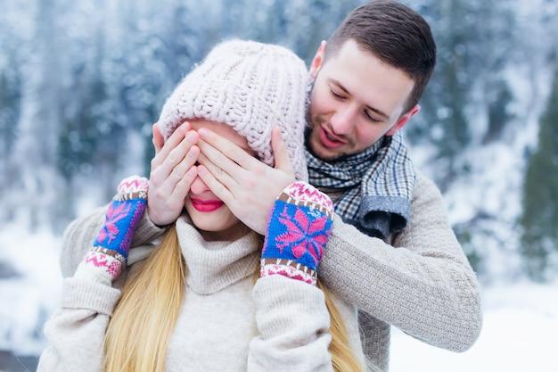 Парень закрывает глаза на девушку руками и что-то ей говорит ей на ухо