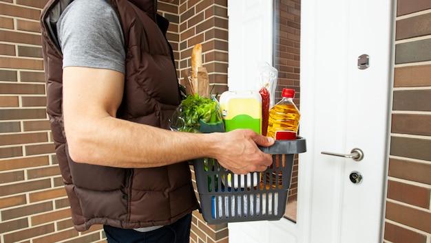 男は食料品がいっぱい入ったバスケットを家のドアに届けます。オンラインショッピング。