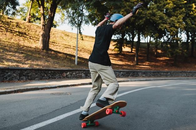 男はスケートボードでトリックをします。高品質の写真