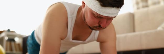 男はフィットネスで体重を減らすアパートのカーペットの上で板の運動をします