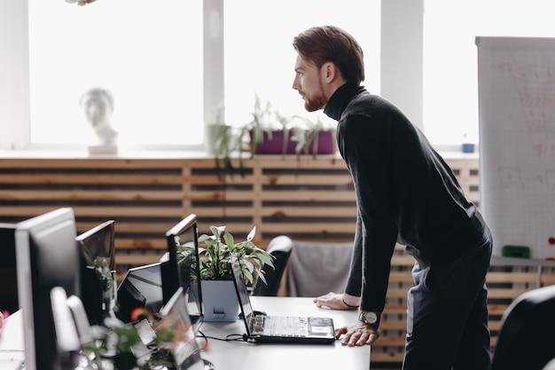 Парень, одетый в повседневную офисную одежду, стоит за столом в современном офисе, оборудованном современной оргтехникой