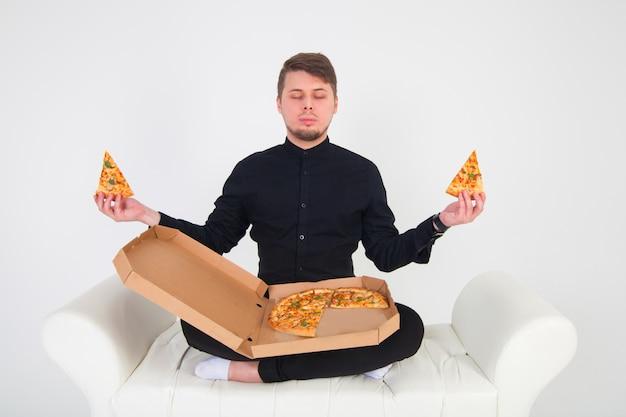 男は黄色い空間でピザを食べて微笑む。
