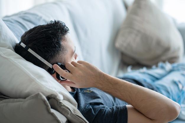 Парень наслаждается музыкой, лежа на диване в наушниках. отдых под музыку.