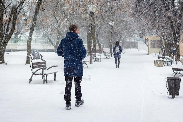 男は降雪時にウィンターパークで女の子を追いかけます_