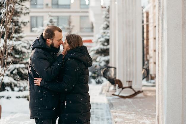Парень нежно целует девушку на фоне заснеженного города. фото высокого качества
