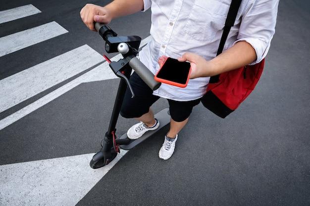 Парень держит в руках мобильный телефон во время езды на электросамокате. заявка на аренду и геолокацию скутера.