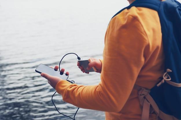 그 남자는 손에 스마트 폰이 달린 휴대용 충전기를 가지고 있습니다. 배낭 호수 배경에 남자는 전원 은행 전화를 청구합니다.