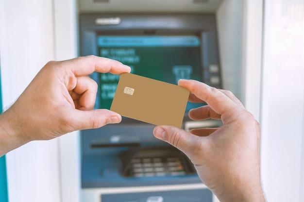 그 남자는 atm 앞에서 은행 카드를 손에 들고 있습니다.