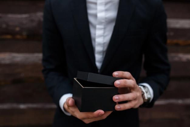 Парень держит в руках коробку, подарок или товар на продажу.