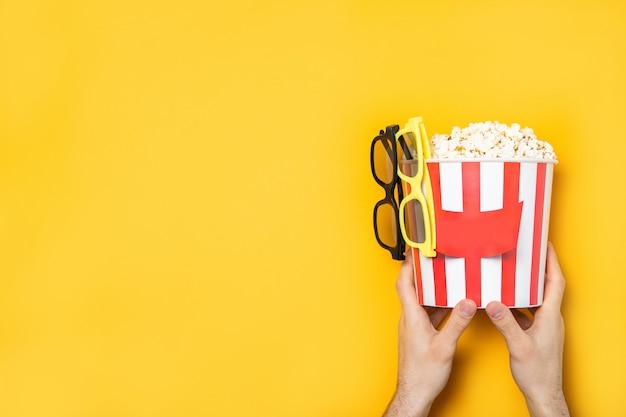Парень держит попкорн в руках на желтой стене. место для текста.