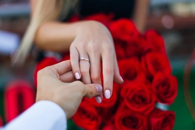 男は女の子の手を握り、薬指に金の指輪を見せます