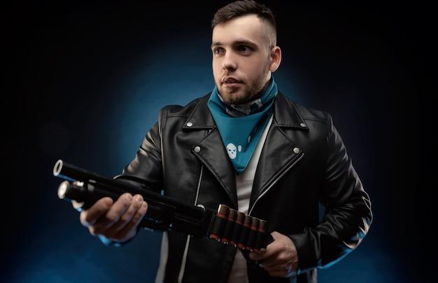 Парень в кожаной куртке с ружьем