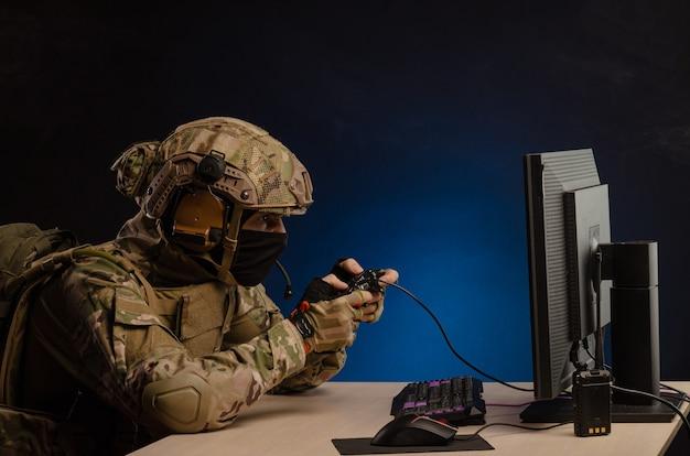 군복을 입은 남자가 조이스틱으로 컴퓨터에서 컴퓨터 게임을 하고 있다