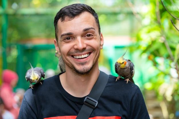 Парень в птичьем парке общается с попугаями. прирученные попугаи выпрашивают еду у туристов.