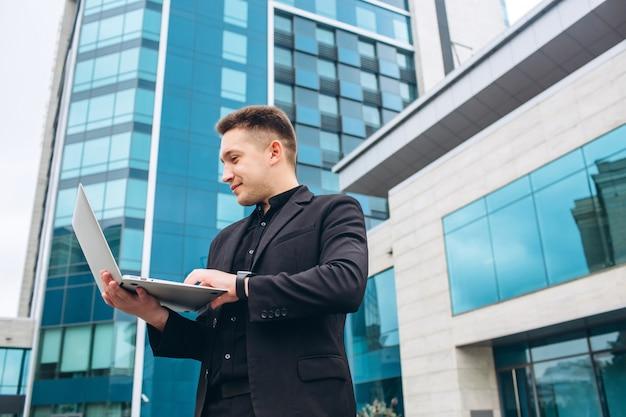 ガラスのモダンなビジネスセンターの黒いスーツを着た男。
