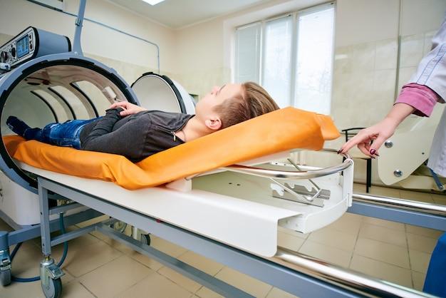 Парень в черной футболке лежит в гипербарической камере кислородной терапии