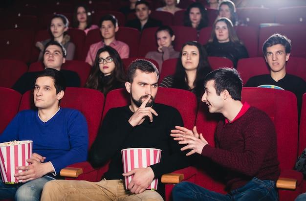 Парень в кино при просмотре фильма мешает разговору